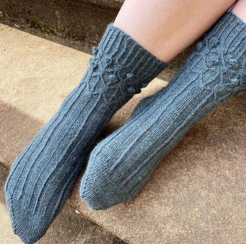 Wollaton Socks by Emily Joy Rickard. Woman wearing pair of socks