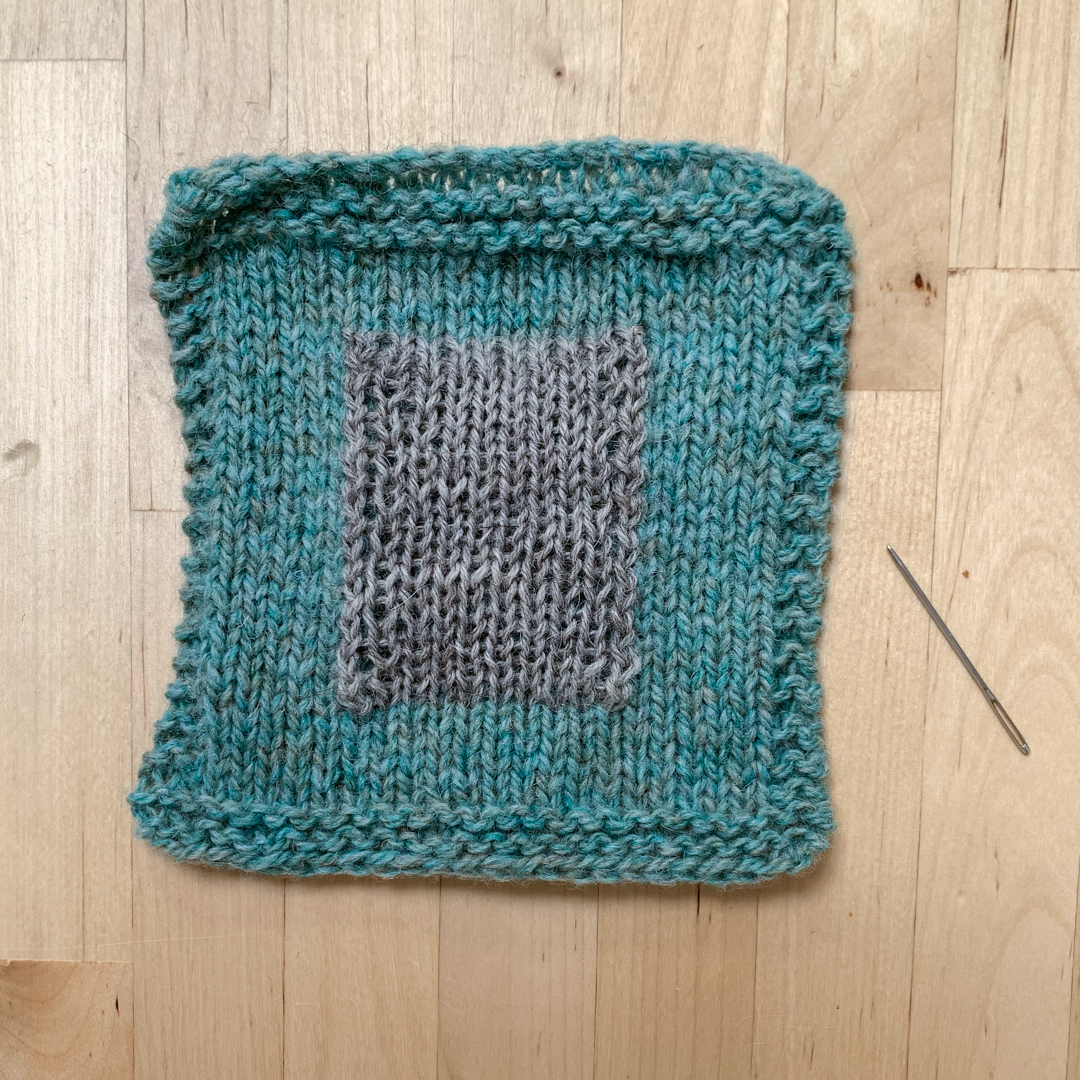 A knitted patch on a hand knit square of fabric