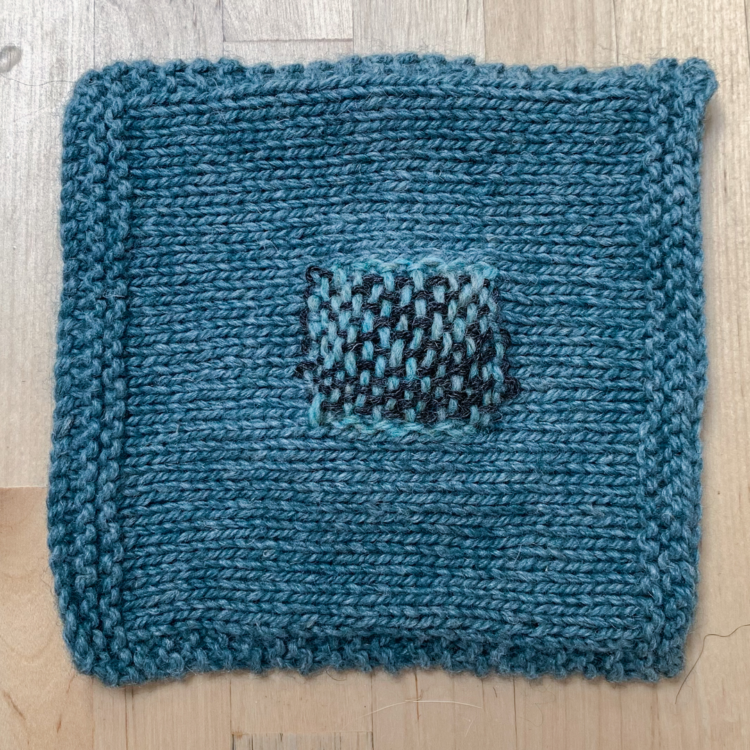 A handknit square of fabric lies on a tabletop. The square has a woven square patch at the centre.