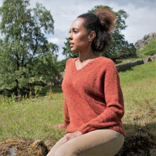 Women sat in a valley, wearing an burt orange knitter sweater