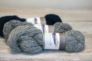 Three hanks of tweed Arranmore Light yarn lie on a table