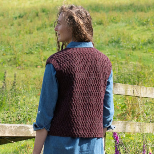 A woman stands in a grassy field with her back to the camera. She wears a handknit sleeveless sweater with an all-over texture stitch on the back.