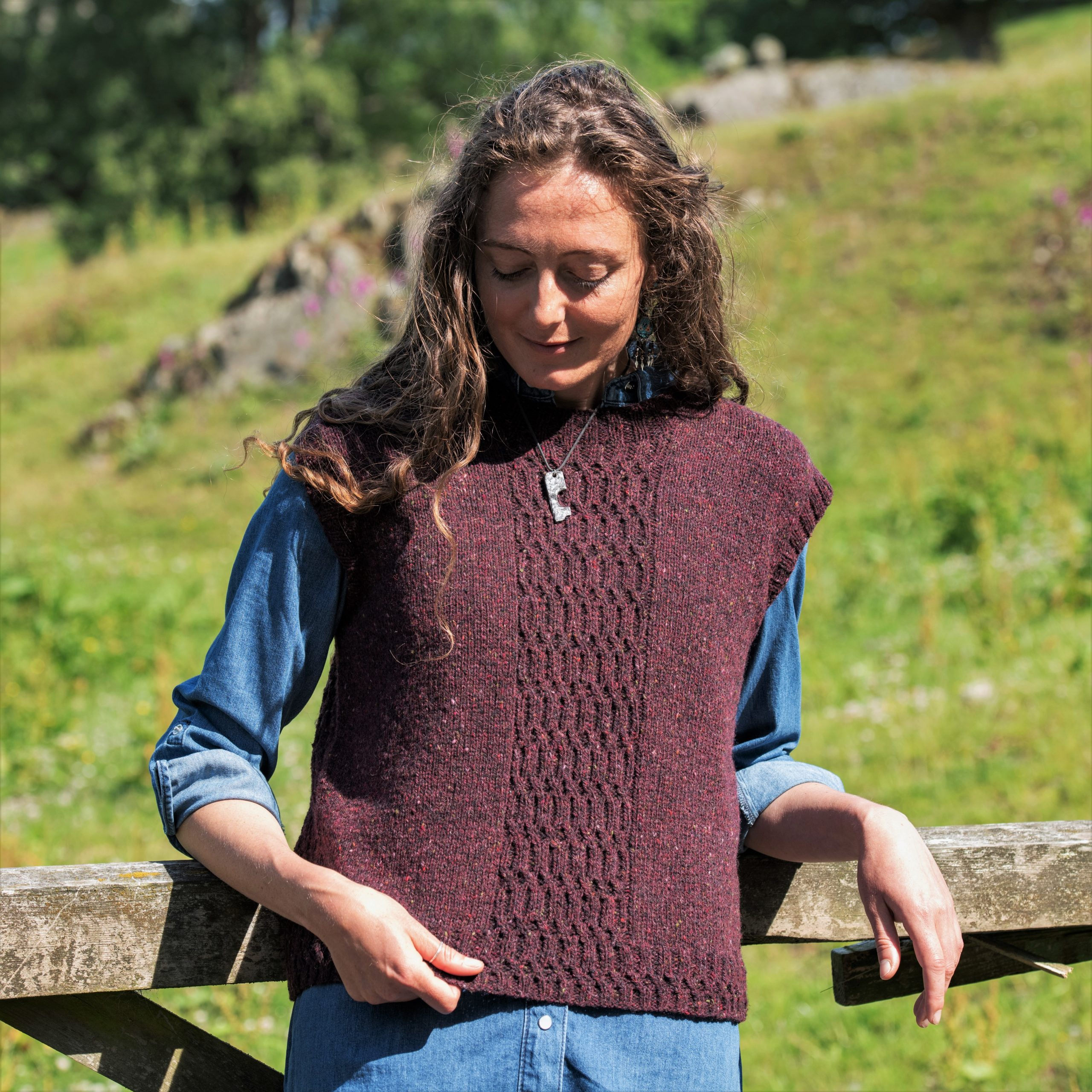 A woman wears a handknit sweater vest over a shirt. the vest has a textured stitch pattern over the centre front.
