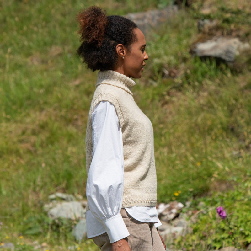 A woman wears a roll-neck handknit vest over a white shirt and stands in a sunlight grassy field