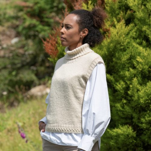 Women standing in the countryside, in a cream roll neck sweater